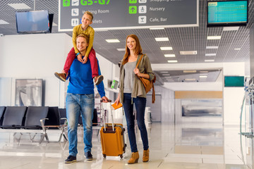 Happy family with suitcase in airport