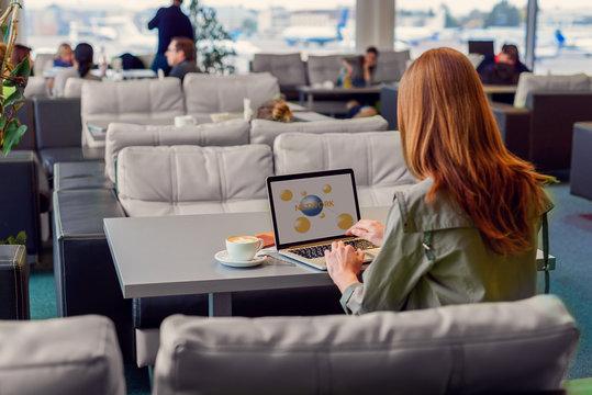Beautiful girl using laptop in airport
