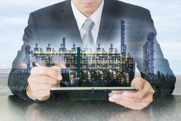 Double exposure of business man working with tablet and gas refinery industry plant as Research of Energy concept.