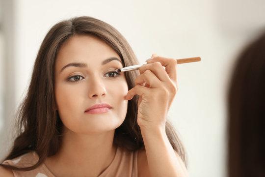 Beautiful girl applying cosmetics in front of mirror