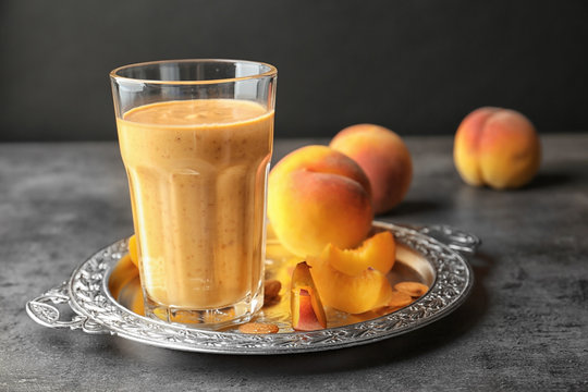 Vintage tray with smoothie and peach on grey table