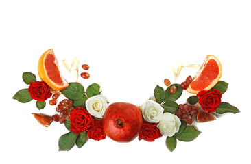 Red pomegranate and floral arrangement on white background
