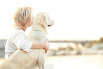 Senior woman with big dog on bund