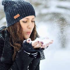 Young woman playing with snow in winter park