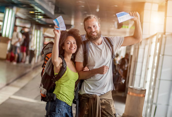 Happy and euphoric couple of backpacker tourists show tickets fo