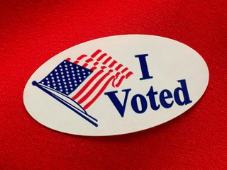"""I voted"" sticker on red fabric"