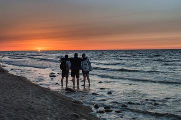 Group of people enjoying sunset at sea shore