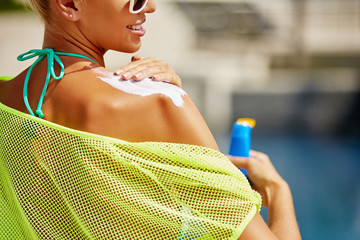 Close up of young tanned woman applying sunscreen on her shoulder