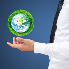 Save the earth by trees. Human hand holding global in soil with green tree for think earth concept. Elements of this image furnished by NASA.