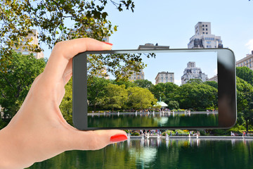 Tourist in Central Park of New York taking a shot at the beautiful landscape