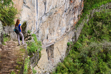 Young woman enjoying the view of Inca Bridge and cliff path near