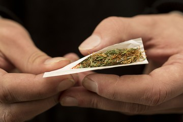 Young man shrinks marijuana cigarette