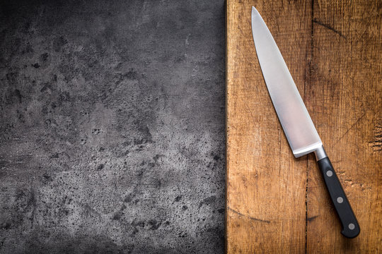 Kitchen knife on concrete or wooden board.
