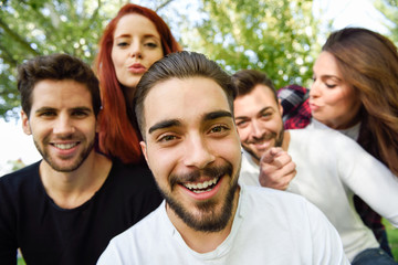 Group of friends taking selfie in urban background