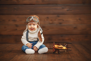 funny baby boy pilot aviator with airplane laughing
