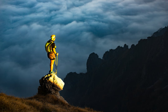 Fantastic sunset in mountains with hiker on a stone where he arr