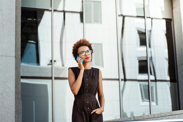 Beautiful african girl smiling speaking on phone walking down city.