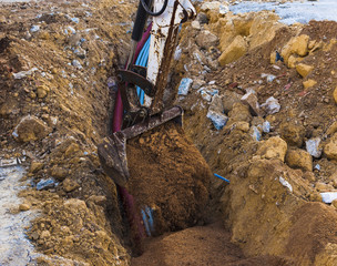 Excavator electrical conduits covered with sand with the assistance of a worker
