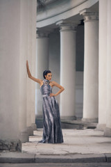 young lady in dress at the entrance of neoclassical building