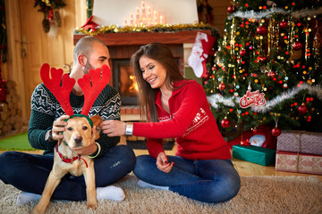 Young couple making fun with dog for Christmas
