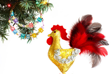 Happy New Year 2017 of rooster card with hand made craft gold rooster and  beaded letter garland  on fir Christmas tree  branch isolated on white background. Copyspace place for your text and logo.
