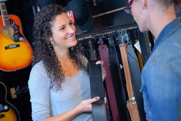 Shop assistant showing guitar strap