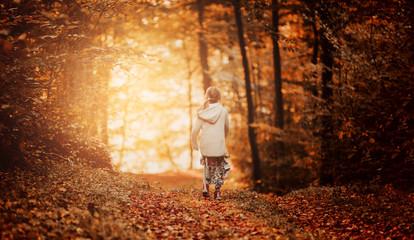 little girl in warm cardigan walking against the background of fallen leaves