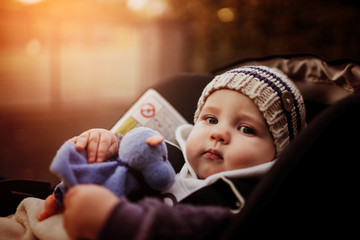 little baby boy sitting in a stroller. baby for a walk in a pram. child autumn outdoors against blurry background