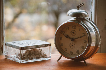 Vintage metal analog alarm clock with Arabic numbers and wind-up mechanism, and a silver jewelry box sitting on a wooden bench with retro background.