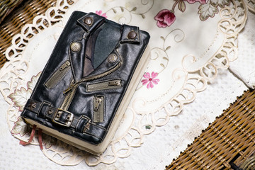 vintage leather jacket style bible cover on the table. Mini biker bible jacket.