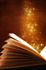 Wall Mural - an open old book with gold stars over grunge background like a concept for magic book