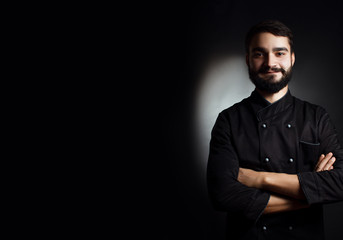 Professional chef with a beard in black uniform on a black background