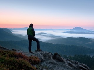Hiker  man on rock watch over creamy mista and foggy morning landscape.
