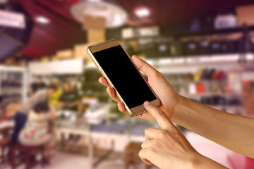 woman hand holding and touch screen of smartphone,tablet,cell phone over camara shopping center