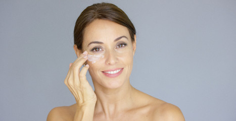 Gorgeous young woman applying face cream to her cheek with her fingertips with a smile in a skincare and beauty concept  close up head and shoulders over grey.