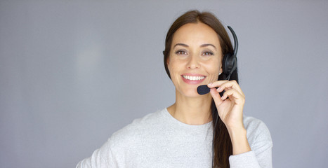 Adorable and beautiful female call center agent speaking with someone on headset. She has smile on her face. Isolated on gray.