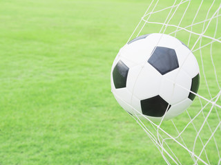 Shooting shot, football in goal net with green grass field background