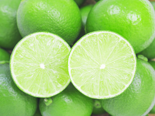 Fresh green limes, full and half slice background