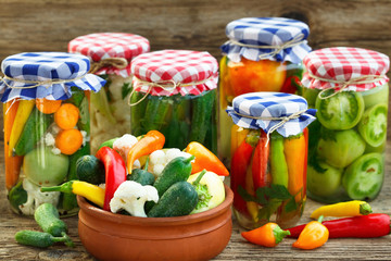 Canned And Fresh Vegetables. Canned Tomatoes, peppers And Pickled Cucumbers In Glass Jars On Wooden Table.