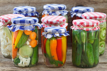 Jars of pickled vegetables on wooden table. Marinated food.