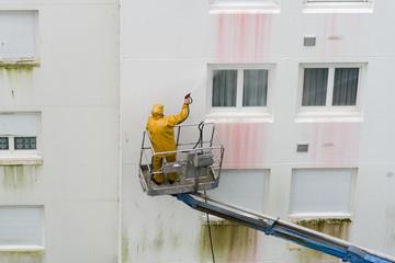 Homme utilisant un nettoyeur haute pression sur une nacelle
