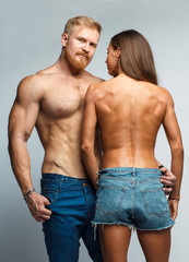 caucasian couple topless woman and brutal man with beard in jeans isolated on studio background