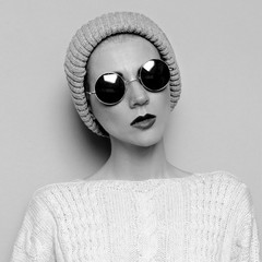 Hipster Girl in style knitted hat and sunglasses