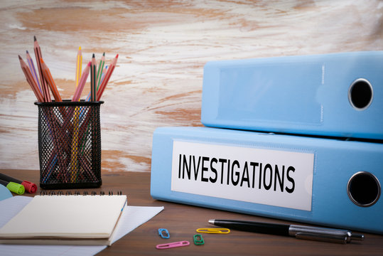 Investigations, Office Binder on Wooden Desk. On the table color