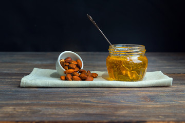 Amber honey and almond nuts on wooden table. Black background. Copy space.