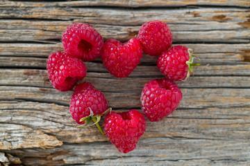 Raspberry heart on wooden surface