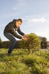 young male gardener working in garden