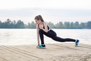 Young woman stretches her legs during training workout exercises