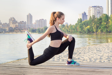 Young woman stretches her legs during fitness workout exercises
