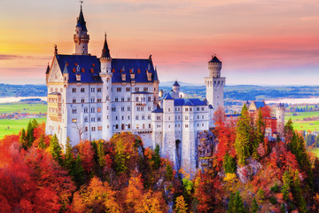 Wall Mural - Germany. Famous Neuschwanstein Castle in the background of trees with yellow and green leaves and valley.
